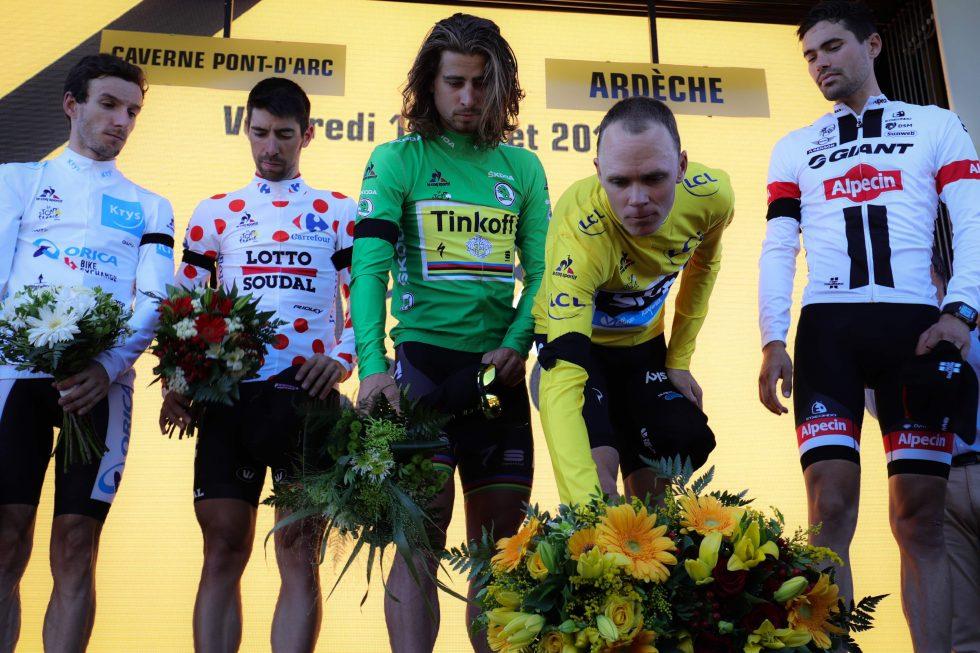 LA NED BLOMSTER: (fra venstre) Adam Yates, Thomas De Gendt, Peter Sagan, Chris Froome og Tom Dumoulin holdt et verdig minutts stillhet på podiet etter den 13. etappen i Tour de France. AFP PHOTO / JEAN-PHILIPPE KSIAZEK