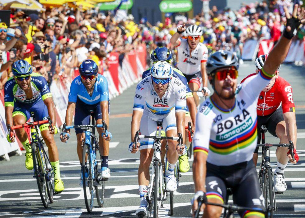 NY KAMP: Kristoff (bak i hvit) ender på femteplass i det slovakiske Peter Sagan løfter hånden i været i mål etter andre etappe i Tour de France i La Roche-sur-Yon søndag. Torsdag venter nye muligheter. Foto: Heiko Junge / NTB scanpix